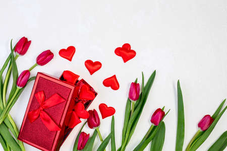 Beautiful red tulips and gift box on a textured white background with a copy of the space. Concept of Valentine's Day, women's day on the eighth of March, mother's Day. Top view, flat lay.