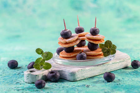 Delicious tiny pancakes and fresh blueberries on skewers. New food trend concept.