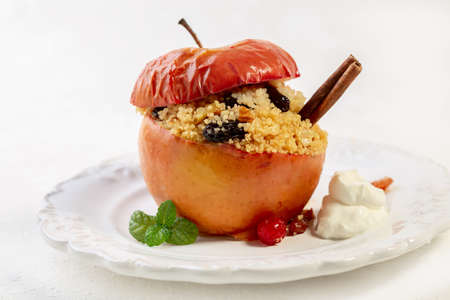 Baked apple with couscous, raisins, cranberries and walnuts served with a cinnamon stick, whipped cream and fresh mint.