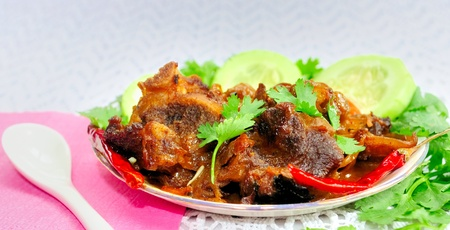 Juicy, delecious Meat Curry (Meat Korma) on a plate with garnishing vegetable and coriender leaves Stock Photo
