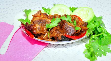 Juicy, delecious Indian dish named Mutton Korma (Mutton Curry, Meat Korma) on a plate with garnishing vegetable and coriander leaves