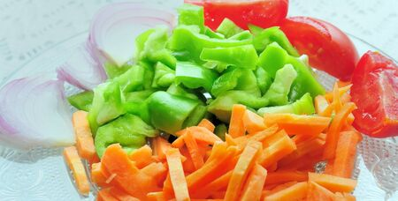 Slices of green capsicum, tomato, carrot and onion, used as ingredient for cooking an Indian dish