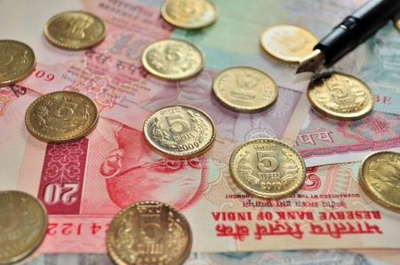 Indian Currency notes of denomination Rs.20, Rs.10, Rs.5 and Coins of denomination Rs.5 with a black fountain pen photo