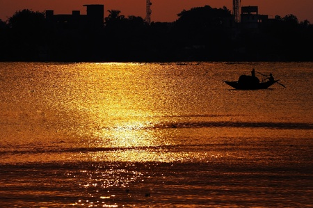 Sunset, Country boat heading towards golden rays, river ganges
