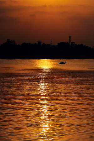 howrah: Sunset, Country boat heading towards golden rays, river ganges