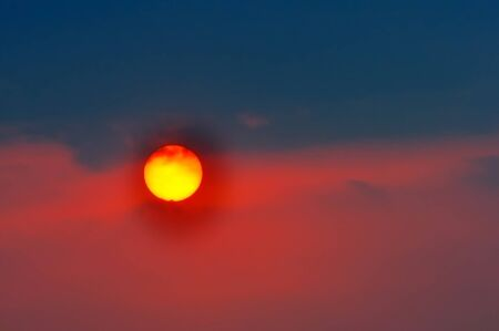 Setting sun with clouds colored red and bluish black Stock Photo