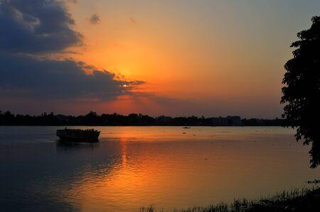 Sunset, boat heading towards horizon, golden rays, river ganges Stock Photo