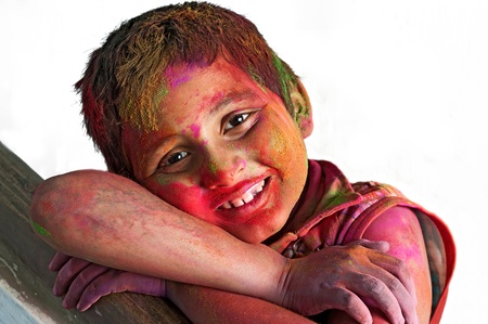 Close up face of young boy playing Holi, smiling with colors, white Background