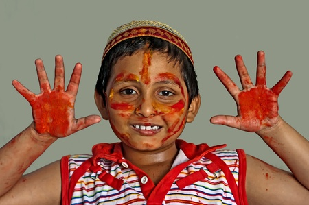 Young boy playing Holi, smiling with colors on face and hands, with cap Stock Photo