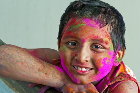 Close up face of young boy playing Holi, smiling with colors on face Stock Photo