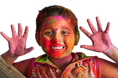 Close up face of young boy playing Holi, smiling with colors on face and hands photo