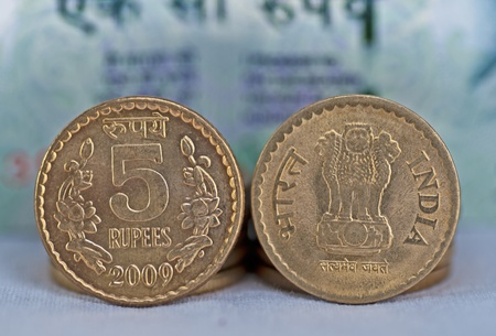 Close up of Indian Coin, 5 rupees, defocussed 100 rupees note in background, isolated, copy space,