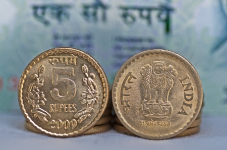 Close up of Indian Coin, 5 rupees, defocussed 100 rupees note in background, isolated, copy space, photo