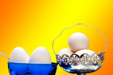 White eggs in glass bowl, basket, spoon, front lit, isolated, Orange and Yellow background, copy space Stock Photo