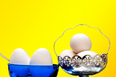 White eggs in glass bowl, basket, spoon, front lit, isolated, Yellow background, copy space Stock Photo