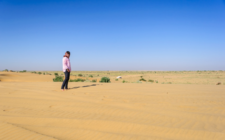 Mature, young Indian lady tourist standing in barefoot in sand, Desert National Park, Rajasthan, copy Space Stock Photo