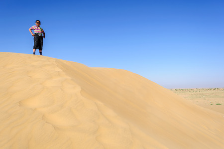 Indian boy, tourist, with binoculars, standing on sand dune  of Desert National Park, Rajasthan, Copy space Stock Photo