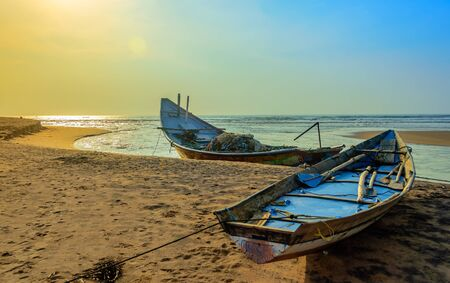 Traditional colorful fishing boat anchored at the confluence of Mahendra Tanaya river and Bay of Bengal, copy space