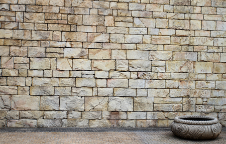 hamam: Bath stone with a brick wall behind.