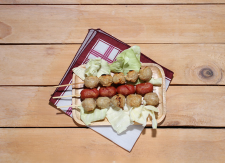 cooked pepper ball: Meatballs in a wooden plate with green leaves on a wooden table.