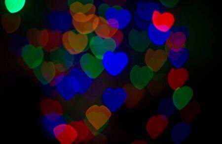 Multi-colored bokeh lights in a heart shape, black scene