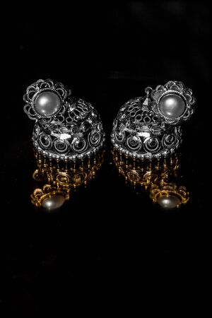 Earring Gold Jewelry Traditional With Stones and Two Golden earrings with reflection . Pair of golden earring with pearl tone on black background. Luxury female jewelry, close-up