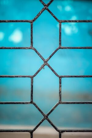 Designed iron rod gate on blue background picture