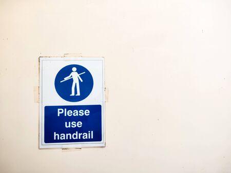 Please use handrail sign poster on wall near escalator.