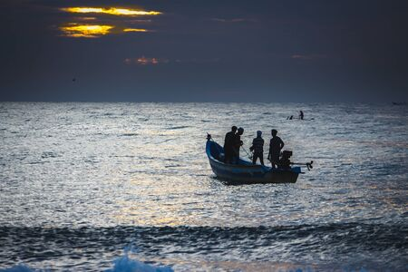 Kovalam, Tamildadu, India - June 13th 2020: Local fishermen start their work at early morning in coast and pulling their fishing boat out of the sea near Chennai. Firsherman on boat at sunsrise, Фото со стока