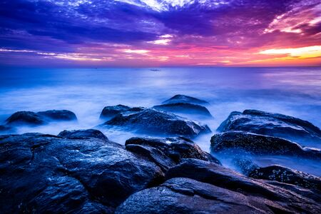 Beautiful sunrise over the beach in long exposure. Moving elements sunrise and wave photography from the rocky beach in india. Red sky in bay of bengal , slow-shutter Sea Waves and Rocks photography.