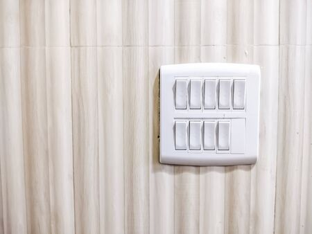 White Light switch on switchboard - Light brown background