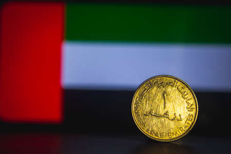 United Arab Emirates Dirham - One Dirham coin of UAE isolated on United Arab Emirates flag background. UAE currency 1 dirham coin with space for text copy