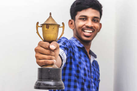 Happiness & achievement concept - Man holding winner trophy on his hand isolated on white background. Man holding a champion Gold cup trophy on hand. Championship prize Trophy . Holding trophy cup Stock Photo