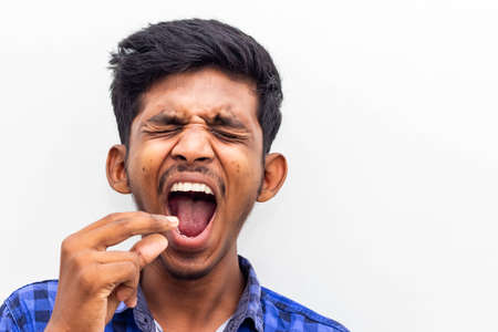 Yawning young boy - Closeup Portrait of yawning man isolated on white background with Copy Space, Student exhausted and tired for studying exam. Sleepy man yawning and closing mouth with his hand.