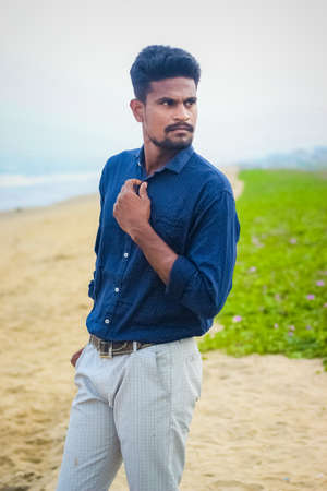 Sexy Indian model posing with wearing formal shirt & pant in sea beach view. Handsome and confident men. Outdoor portrait of smiling young Asian indian man on the beach. 免版税图像