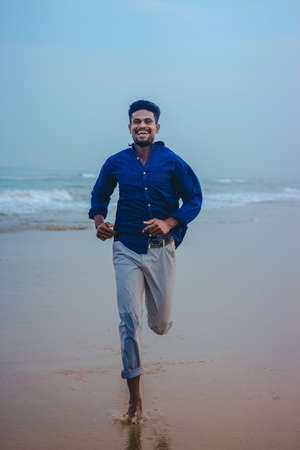 Indian men model running on beach sand in sea view background. Handsome and confident men. Outdoor portrait of running young Asian indian man on the beach. 免版税图像