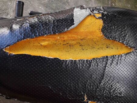 The old motorcycle seat is broken and can see the yellow sponge inside. Have to repair, change leather, new seats Imagens