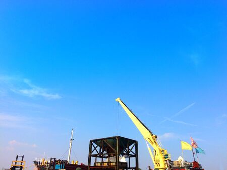 Large yellow scoop Are scooping the white Urea chemical fertilizer From a pontoon boat to unload 写真素材