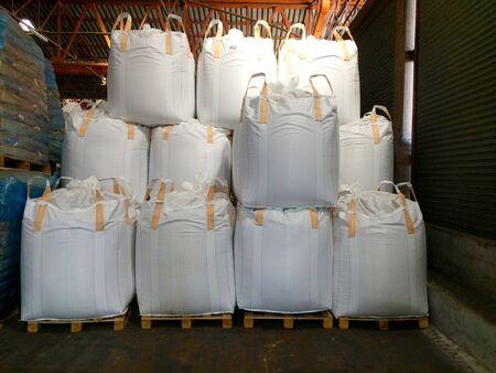 Engrais à base d'urée en tas de stocks de sacs géants dans l'entrepôt en attente de livraison aux agriculteurs et aux exportations. Banque d'images