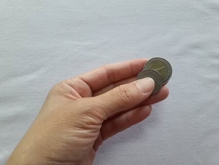 The woman's hand and Thai baht coins are in the hands on a white cloth background. Stock fotó - 134773955