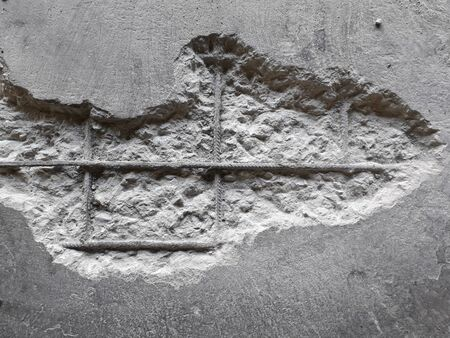 Die beschädigte Wand ist an der inneren Stahlstange sichtbar. Der Putz sollte mit Mörtel repariert werden, damit er funktioniert. Standard-Bild