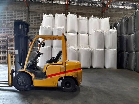 Big yellow car loader and White hemp sacks containing chemical fertilizer in the warehouse.