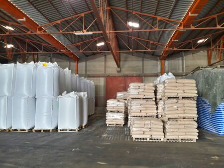 Chemical fertilizers Packed in stacked sacks with clear plastic wrapped around stacked on wooden pallets orderly. In the warehouse waiting for delivery Фото со стока