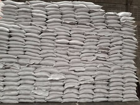 White sacks contain urea and chemical fertilizers stacked in the warehouse, waiting for delivery to customers. Stock Photo