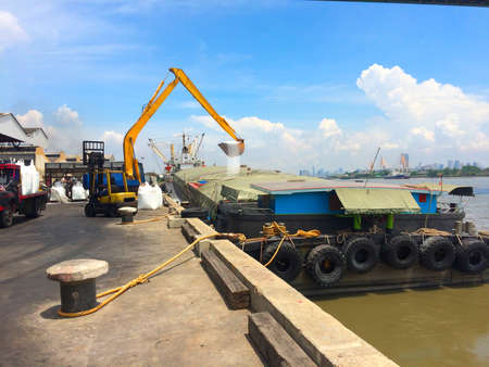 Large yellow scoop are scooping the white Urea chemical fertilizer from a pontoon boat to unload Archivio Fotografico