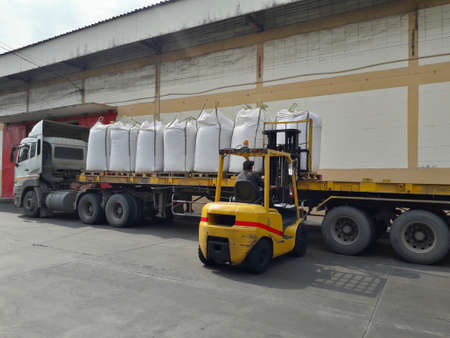 Trailer loading sack goods to customers.