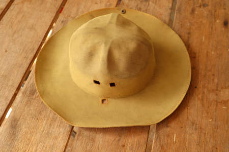 Old brown scout hat, placed on a wooden floor.