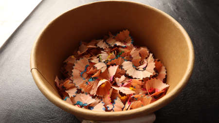 Pencil shavings Many pieces of pencil shavings lay on top of brown paper.