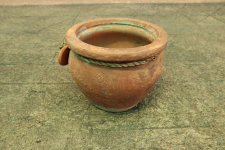 Brown pottery is placed on the cement floor.