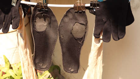 Washed old shoe pads with pegs to dry in the sun.